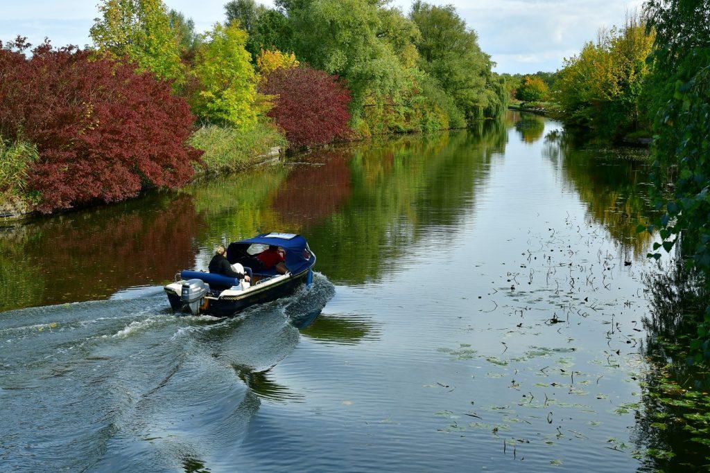 Klein motorbootje vaart door het Streekbos